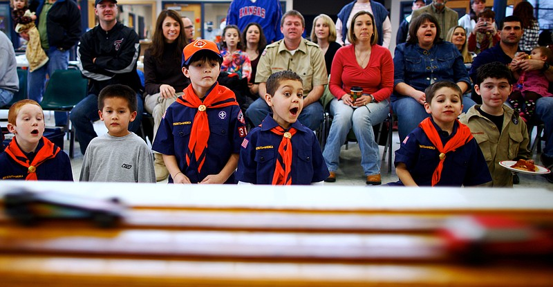 Members of Cub Scout Pack 3071 watch as race cars fly down the track during the pack's annual Pinewood Derby on Saturday at Prarie Park School. Each car was required to weigh below five ounces.