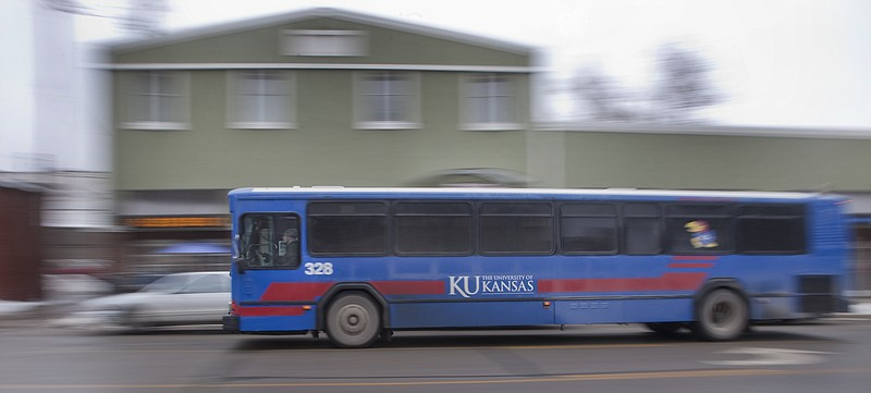 A KU bus enters downtown headed for a stop for passengers near Ninth and Massachusetts streets Friday. Public meetings begin this week for the latest recommendations for consolidating and possibly adjusting transit services involving the Kansas University and city bus services.